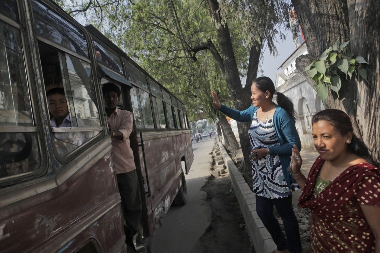 Nepalese women wave at children traveling to school in a school bus, as thousands of schools across the districts worst hit by two major earthquakes in Nepal reopened Sunday, in Kathmandu, Nepal, Sunday, May 31, 2015. With most school buildings damaged or unsafe, the Education Ministry ordered that classes be held in temporary classrooms. According to a UNICEF statement, 32,000 classrooms were destroyed and 15,352 classrooms were damaged after the two major earthquakes in Nepal. (AP Photo/Niranjan Shrestha)