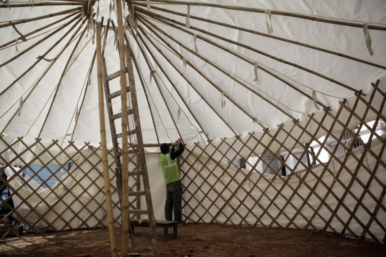 A Nepalese man constructs a tent which will serve as a temporary school, as thousands of schools across the districts worst hit by two major earthquakes in Nepal reopened Sunday, in Kathmandu, Nepal, Sunday, May 31, 2015. With most school buildings damaged or unsafe, the Education Ministry ordered that classes be held in temporary classrooms. According to a UNICEF statement, 32,000 classrooms were destroyed and 15,352 classrooms were damaged after the two major earthquakes in Nepal. (AP Photo/Niranjan Shrestha)