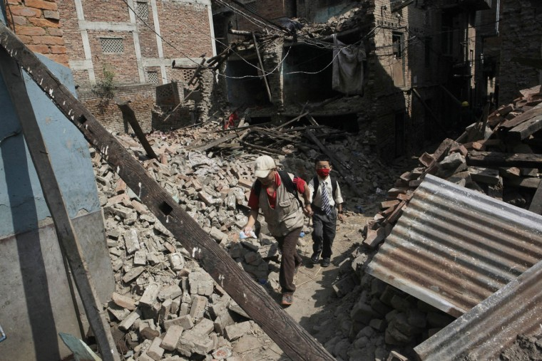 A Nepalese man leads his son past debris towards his school, as thousands of schools across the districts worst hit by two major earthquakes in Nepal reopened Sunday, in Kathmandu, Nepal, Sunday, May 31, 2015. With most school buildings damaged or unsafe, the Education Ministry ordered that classes be held in temporary classrooms. According to a UNICEF statement, 32,000 classrooms were destroyed and 15,352 classrooms were damaged after the two major earthquakes in Nepal. (AP Photo/Niranjan Shrestha)
