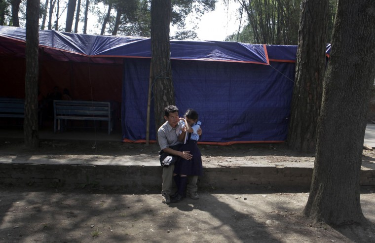 A Nepalese man comforts his crying daughter at her school premise, as thousands of schools across the districts worst hit by two major earthquakes in Nepal reopened Sunday, in Kathmandu, Nepal, Sunday, May 31, 2015. With most school buildings damaged or unsafe, the Education Ministry ordered that classes be held in temporary classrooms. According to a UNICEF statement, 32,000 classrooms were destroyed and 15,352 classrooms were damaged after the two major earthquakes in Nepal. (AP Photo/Niranjan Shrestha)