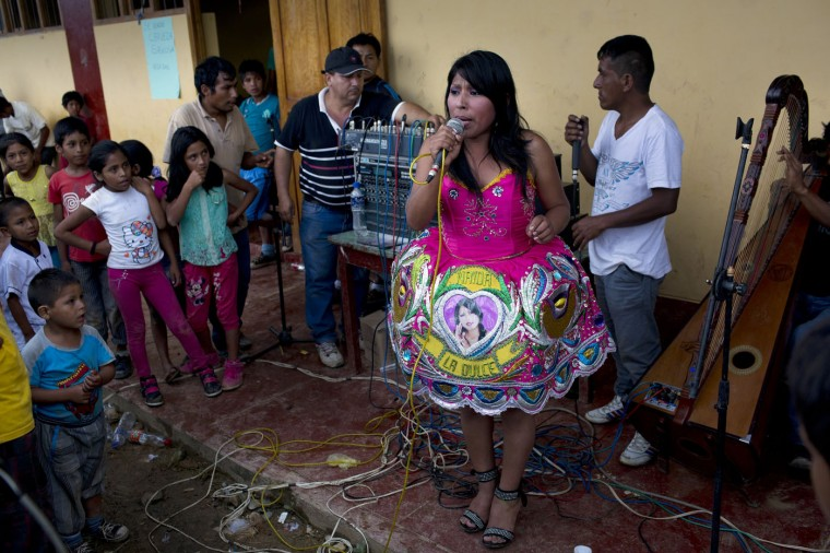In this March 15, 2015 photo, huayno singer Nanda la Dulce performs during a multi-village soccer tournament, in La Mar, province of Ayacucho, Peru, located in the remote Apurimac, Ene and Mantaro river valley, where 60 percent of Peruís cocaine originates there. Huayno traditional Andean folk music. (AP Photo/Rodrigo Abd)