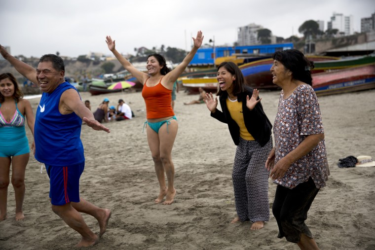 "In this May 8, 2015 photo, people smile during a laugh therapy session on Fishermen's Beach in Lima, Peru. Natural therapy promoter Jose Cusquisiban organizes therapy groups and has his patients jog barefoot on the beach sand. ""Then we make a harmonious circle of prayer, afterward we sing, we practice laugh therapy, we hug and finally we enter the sea and teach those who don't know how to swim,"" Cusquisiban said. (AP Photo/Rodrigo Abd)"