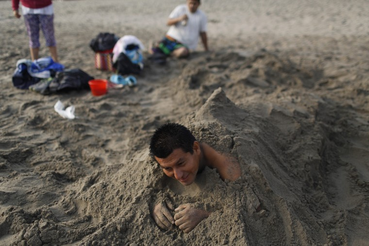 "In this April 25, 2015 photo, Victor Villanueva rests in the sand on Fishermen's Beach during his therapeutic session of ""sand therapy"" on the coast of the Pacific Ocean in Lima, Peru. Villanueva is one of many along Lima's coast practicing thalassotherapy, in search of relief from the ailments doctors have been unable to cure. (AP Photo/Rodrigo Abd)"