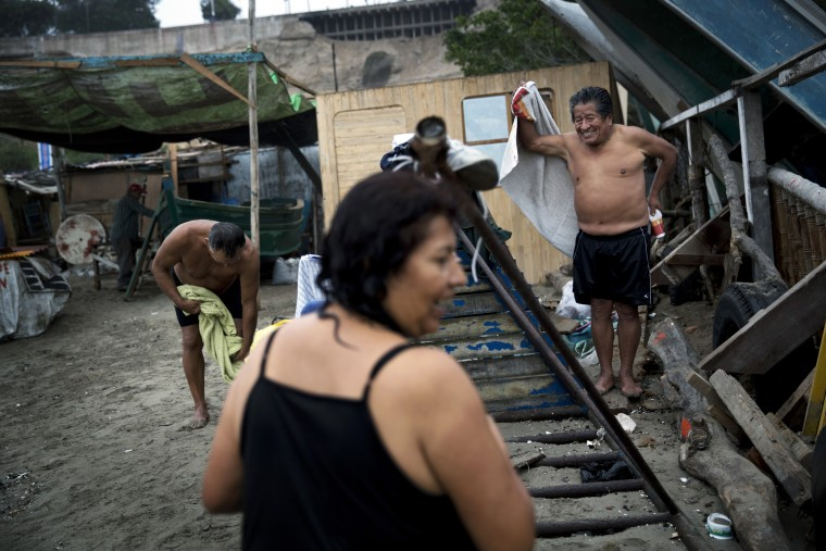 "In this May 13, 2015 photo, people get dressed on Fishermen's Beach after swimming in the Pacific Ocean in Lima, Peru. Under the capital's overcast skies, bathers practice thalassotherapy, which derives from the Greek ""thalasso,"" for ""sea,"" and draws on the ocean's healing properties. (AP Photo/Rodrigo Abd)"