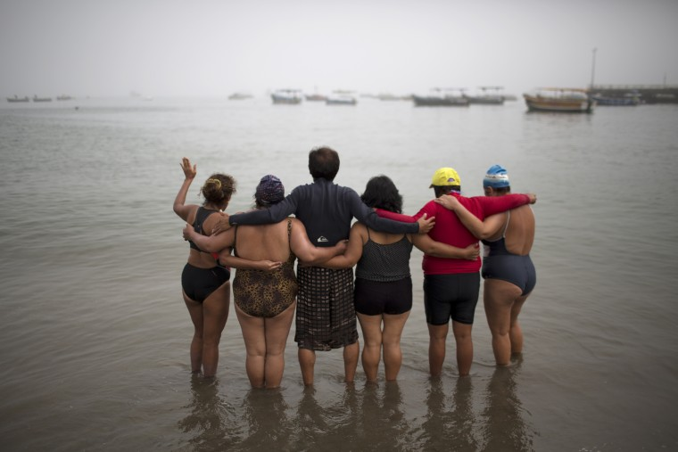 "In this April 9, 2015 photo, a therapy group who have become friends pray on Fishermen's Beach before taking a therapeutic swim in the Pacific Ocean in Lima, Peru. ""The sea is the pharmacy of humanity,"" said natural therapy promoter Jose Cusquisiban, who organizes therapy groups. ""It has many minerals, vitamins."" (AP Photo/Rodrigo Abd)"