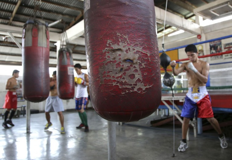 In this April 22, 2015, photo, a worn punching bag hangs at the training area where Filipino boxers practice at a boxing gym in suburban Paranaque, south of Manila, Philippines. Many young boxers look to boxing as a ticket out of harsh lives and uncertainties. (AP Photo/Aaron Favila)