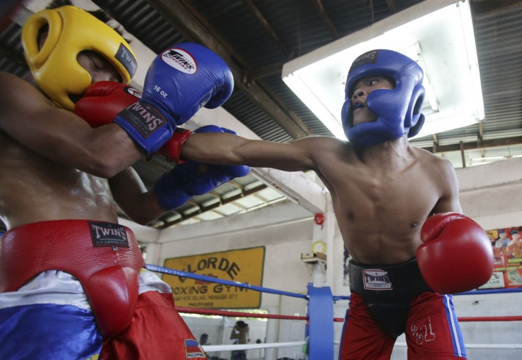 In this April 22, 2015, photo, Filipino boxer Rolly Sumalpong, right, lands a punch on Robert Landero during their training at a boxing gym in suburban Paranaque, south of Manila, Philippines. Many young Filipinos aspire to become successful boxers throughout the country. (AP Photo/Aaron Favila)