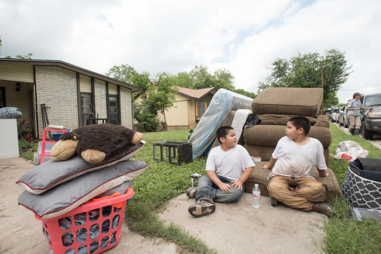 Kino Rodriguez, 8, left, and Israel Rodriguez, 7, sit outside their families flood-damaged home and discuss their experiences with the flooding from the night before on Sunday May 24, 2015, in San Marcos, Texas. Record rainfall was wreaking havoc across a swath of the U.S. Midwest on Sunday, causing flash floods in normally dry riverbeds, spawning tornadoes and forcing at least 2,000 people to flee. (Erika Rich/Austin American-Statesman via AP)