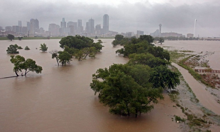 With downtown Dallas in view, water from the Trinity River floods the area below the Sylvan Avenue bridge Monday, May 25, 2015, in Dallas. Several people were reported missing in flash flooding from a line of storms that stretched from the Gulf of Mexico to the Great Lakes. (Louis DeLuca/The Dallas Morning News via AP)