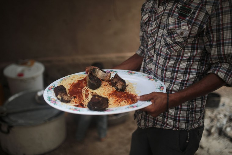 A Yemeni refugee collects a meal for his family, at an orphanage that has been turned into a center for Yemeni refugees,in Obock, northern Djibouti. (AP Photo/Mosa'ab Elshamy)