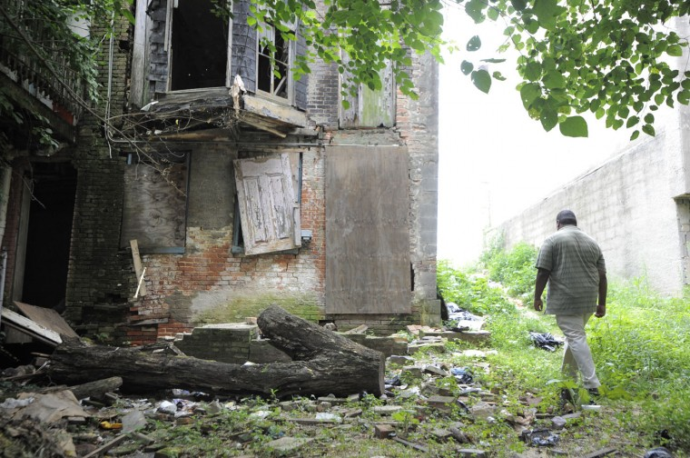 8/21/14: Kelly Little the Executive Director of Druid Heights Community Development Corp. walks behind a home in the 2200 block of Druid Hill Ave. that they have tried to clean up. (Lloyd Fox/Sun Photographer)