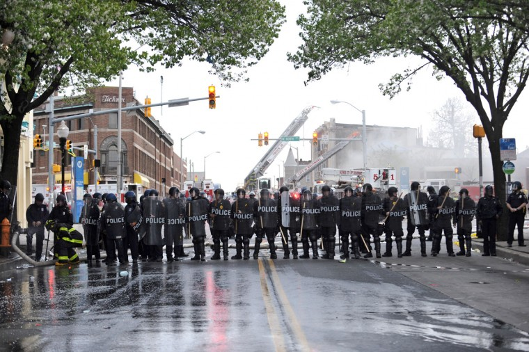 4/27/15: As fire trucks put out the fire at CVS in the background, police form a line across North Ave. and Pennsylvania Ave. to contain rioting on the day of Freddie Gray's funeral. Gray died in police custody on April 19th. (Algerina Perna/Baltimore Sun)