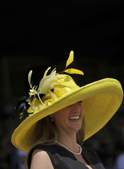 Gerry Harris, Glen Arm, wears a yellow straw hat with feathers and a black linen blend dress her husband, Mike Harris, picked out for the Preakness. The outfit is from Ellie Boutique in Ruxton. (Kim Hairston/Baltimore Sun)