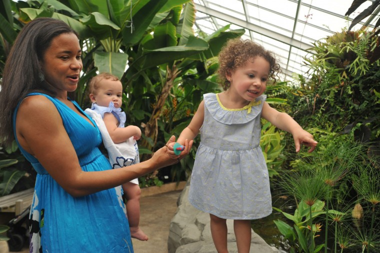 Tropical Mother's Day: Shani Walter of Baltimore, left, came to the Howard Peters Rawlings Conservatory with her family on Mother's Day. She is holding her 10-month old daughter, Kara Walter, while her older daughter, Kate Walter, 2 1/2 years old, spots fish in the Tropical House. They visited the Conservatory after a family brunch for Mother's Day. (Amy Davis/Baltimore Sun)