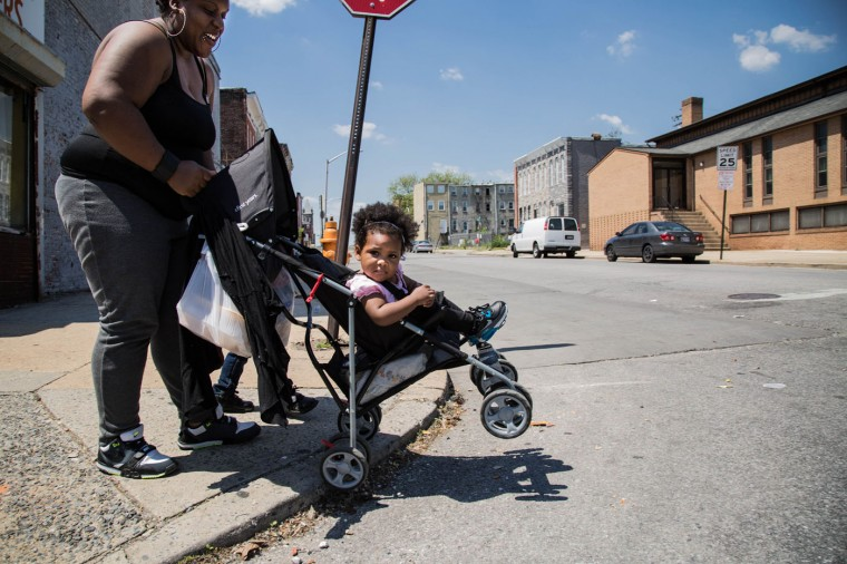 A woman pushes her child in a stroller in the Sandtown-Windchester neighborhood on May 4, 2015 in Baltimore, Md. (Jessica Koscielniak/McClatchy DC/TNS)