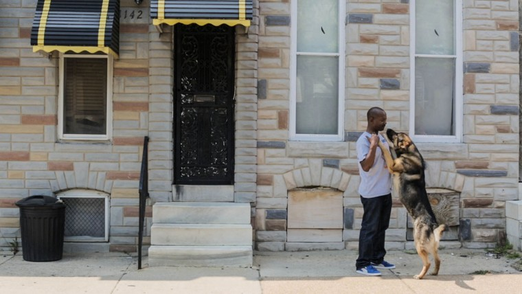 Doni Glover kisses his dog Pharaoh outside his Sandtown-Winchester home on May 5, 2015 in Baltimore, Md. (Jessica Koscielniak/McClatchy DC/TNS)