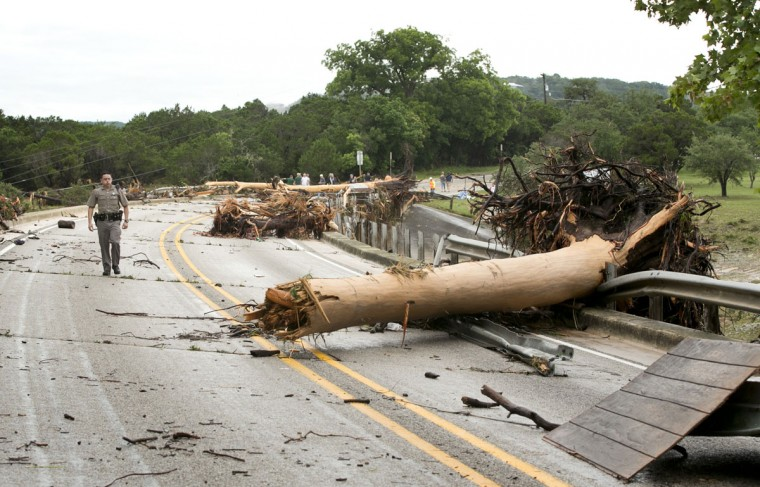 DPS Trooper Marcus Gonzales walks on the Hwy 12 bridge over the Blanco River in Wimberley, Texas, which was blocked by large trees after the flood on Sunday, May 24, 2015. (Jay Janner/Austin American-Statesman/TNS)