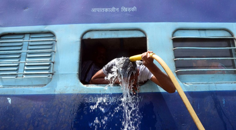 An Indian commuter uses the train's hose pipe to cool down on May 24, 2015 at the railway station in Allahabad, India. Most of northern India has been reeling under a heat wave with temperatures soaring to over 46 degree Celsius. (Prabhat Kumar Verma/Zuma Press/TNS)