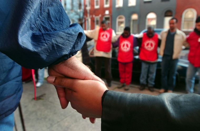 04/04/2002: Druid Heights Peace Patrol members Ionie Gordon (left) and Catherine Trotter clasp hands as the group prays before they walk through neighborhoods to spread information to reach out to people who are having drug- related problems Thu., Apr. 4, 2002. (Baltimore Sun/Karl Merton Ferron)