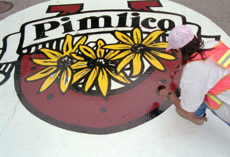 "Benneta Bullock, from the sign shop, Dept. of Public Works, puts some finishing touches to a ""Pimlico"" sign being painted on Northern Parkway at the intersection with Preakness Way, near the racetrack. The signs are painted every year prior to the running of the Preakness. (Robert K. Hamilton/Baltimore Sun, 1994)"