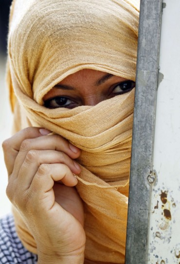 A woman from the Ghajar (gypsy) community looks on in the Diwaniya village, south of Iraq, on May 1, 2015. The Ghajar people, who have their own language, used to be known as entertainers, making their living from singing and dancing. But in the years after now-executed dictator Saddam Hussein came to power, their opportunities for work dwindled. Following Saddam's ouster in 2003, the Ghajar people have been given IDs, making them eligible to vote in Iraqi elections. (AFP Photo/Haidar Hamdani)