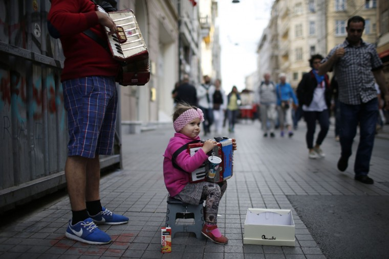 People walk past a musician accompanied by a child playing music for money in Istanbul's main Istiklal Street, Turkey, Thursday, 28 May, 2015. (AP Photo/Emrah Gurel)