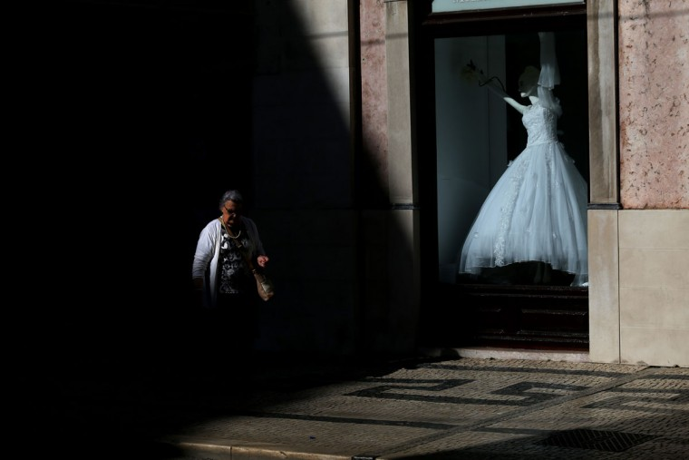 A woman walks past a shop displaying a bridal dress in the Baixa neighborhood of Lisbon, Portugal on Thursday, May 7, 2015. (AP Photo/Francisco Seco)