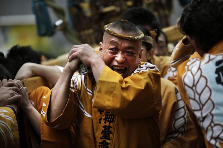 Carrying a portable shrine on their shoulders, participants all clad in traditional happi coats, parade through precincts of the Kanda Myojin shrine during the annual summer festival in Tokyo, Saturday, May 9, 2015. (AP Photo/Eugene Hoshiko)