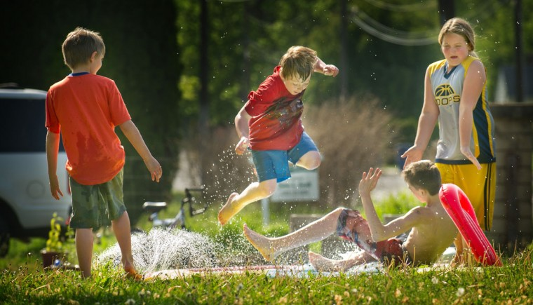Dominick Peters, 9, leaps to avoid a collision with Dylan Logan, 13, as wet slippery fun was being had on a beautiful spring day, Monday, May 4, 2015, in Walla Walla, Wash. Looking on are Brody Logan, 8, left, and Haley Logan, 10, right. (Greg Lehman/Walla Walla Union-Bulletin via AP)