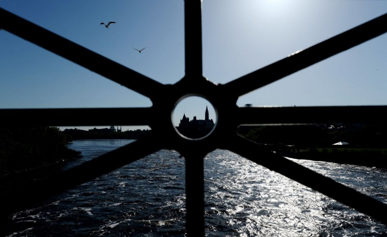 Parliament Hill, in Ottawa, is framed in the railing of the Portage Bridge in this view in Gatineau, Quebec, on Thursday, May 14, 2015. (Sean Kilpatrick/The Canadian Press via AP)