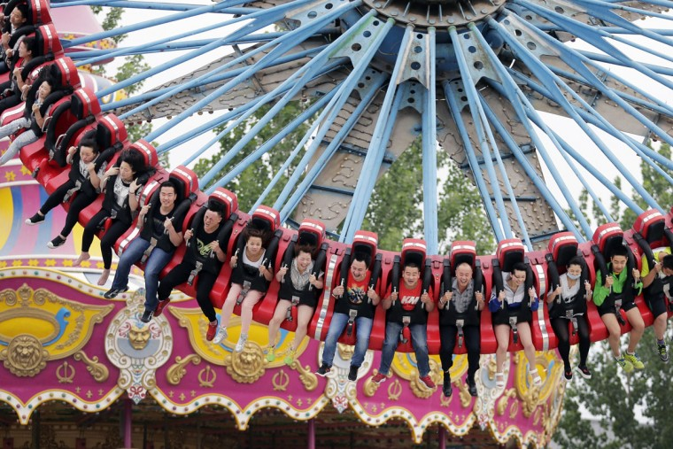 People ride on an amusement machine at Xiedao's theme park during a May Day holiday in Beijing, China, Friday, May 1, 2015. Millions of Chinese are taking advantage of the May Day holidays to visit popular tourist sites. (AP Photo/Andy Wong)