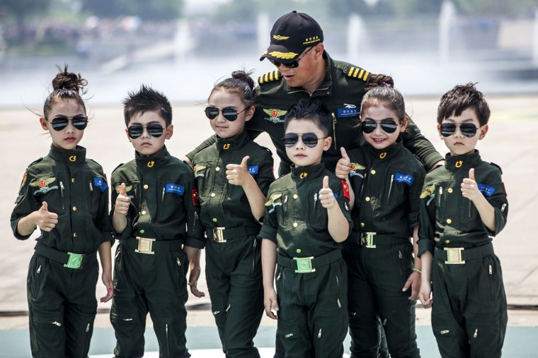 In this photo taken Monday, May 25, 2015, child models wearing flight jackets pose with a pilot for photos during an aviation show in Anyang in central China's Henan province. (Color China Photo via AP)