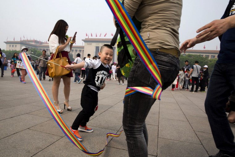 A child plays with a colored ribbon during a visit to Tiananmen Square in Beijing, Friday, May 1, 2015. Millions of Chinese are taking advantage of the May Day holidays to visit popular tourist sites. (AP Photo/Ng Han Guan)