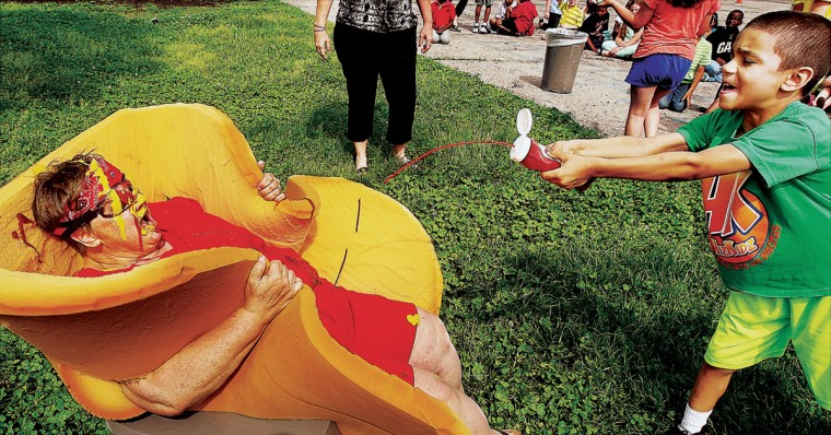 """A student, right, squirts ketchup on Eunice Smith School social skills tutor Sherry Droste as she sits in a chair while wearing a foam rubber """"bun"""" to be a human hot dog Wednesday May 27, 2015, in Alton, Ill. The school allowed students to each dump one condiment of ketchup, mustard, relish, chili or cheese on Droste as a reward for receiving one or fewer disciplinary referrals in the last month of school. (John Badman/The Telegraph via AP)"""
