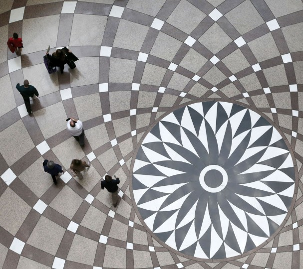Pedestrians walk through the food court at the Thompson Center, Monday, May 4, 2015, in Chicago. (AP Photo/Charles Rex Arbogast)