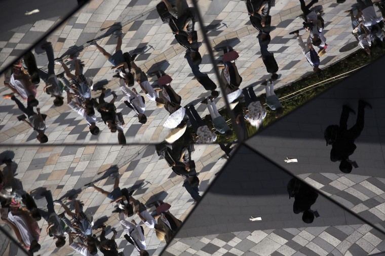 Pedestrians are reflected on a mirror ceiling of a shopping mall in Tokyo, Wednesday, May 27, 2015. (AP Photo/Eugene Hoshiko)