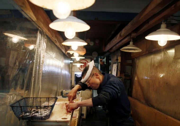 A fish dealer cleans fish in Tsukiji fish market, a well-known for a large wholesale market for fish, fruits and vegetables in Tokyo, Thursday, May 28, 2015. The market's auction of tuna early morning is one of major attractions to visitors and tourists. (AP Photo/Shuji Kajiyama)
