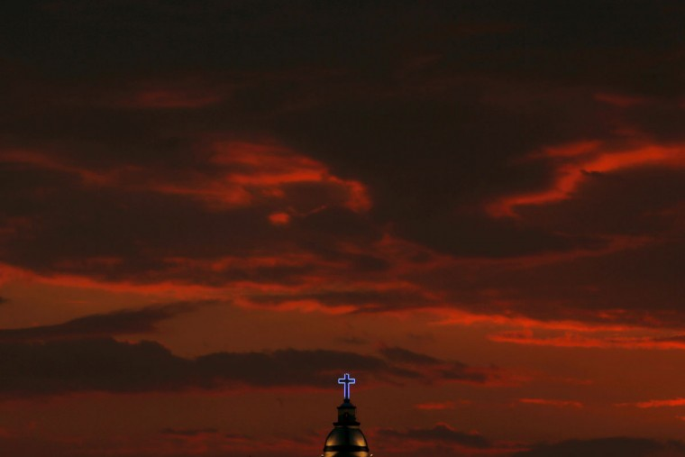 "A neon light outlines the cross on top of the bell tower of the Santa Maria Magdalena Church, Saturday, May 2, 2015, in Tepexpan, Mexico. The town will kick off its annual patronage celebration to venerate the town's saint ""El SeÒor de Gracias"" on May 3. (AP Photo/Julio Cortez)"