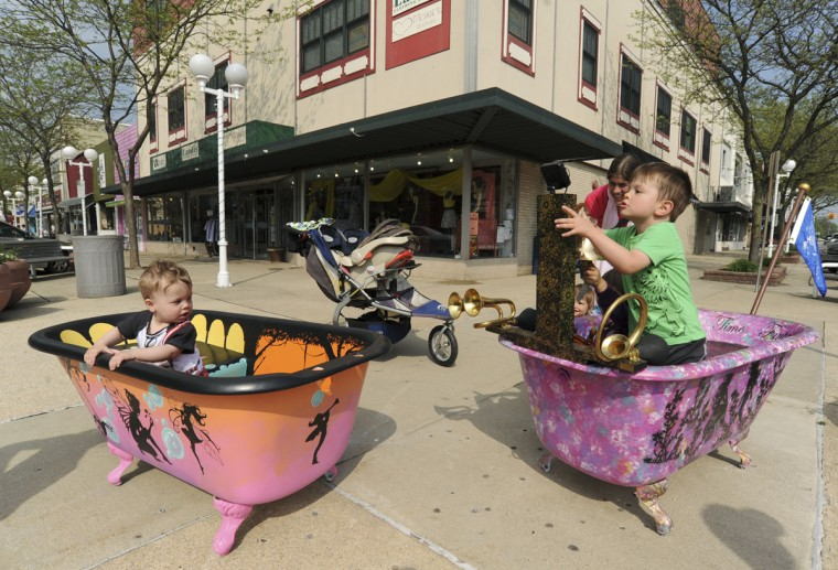 "Ten-month-old Micah Long, left, from St. Joseph, Mich., joins his brother, Asa Long, 3, as they play on pieces in the newest public art project Friday, May 15, 2015, in downtown St. Joseph, Mich. Fairy Good Bubble Bath, left, created by artist John Foster and Bath Time Fantasy, right, by Shannon and Chris Lockman and Kirstin Krieger, are among the 22 new pieces in this year's project titled ""Splishin' and a Splashin'."" (Don Campbell/The Herald-Palladium via AP)"