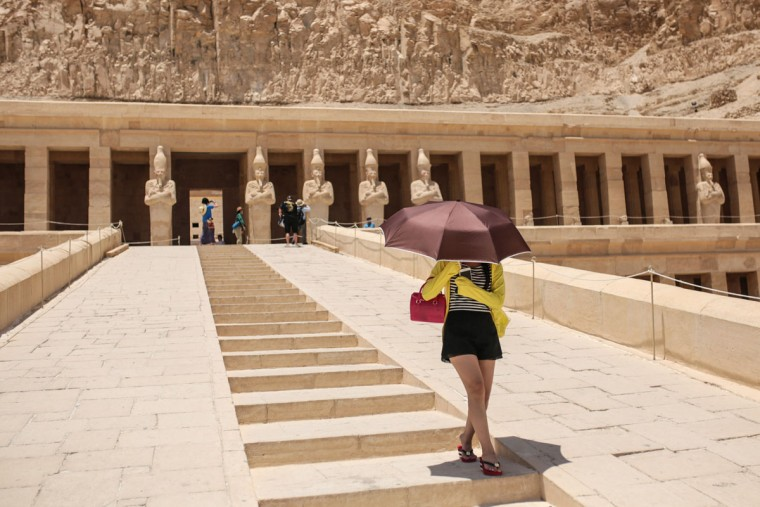 A tourist shelters from the sun under an umbrella at the ancient temple of Hatshepsut, on the west bank of the Nile River, in Luxor, 510 kilometers (320 miles) south of Cairo, Egypt, Saturday, May 2, 2015. (AP Photo/Mosa'ab Elshamy)