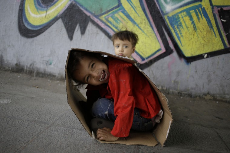 Yara, 5, and her brother Youssef, 16 months, hide inside a cardboard box as they play under a bridge while their mother sells tissue in Cairo, Egypt, Thursday, May 14, 2015. (AP Photo/Hassan Ammar)