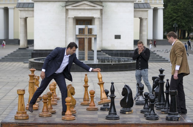 In this Thursday, May 28, 2015 photo, a man laughs as others play chess with oversized pieces on a public entertainment board, in Chisinau, Moldova. The chess game is a popular pastime in parks around the capital. Most players use their own chessboards. (AP Photo/Vadim Ghirda)
