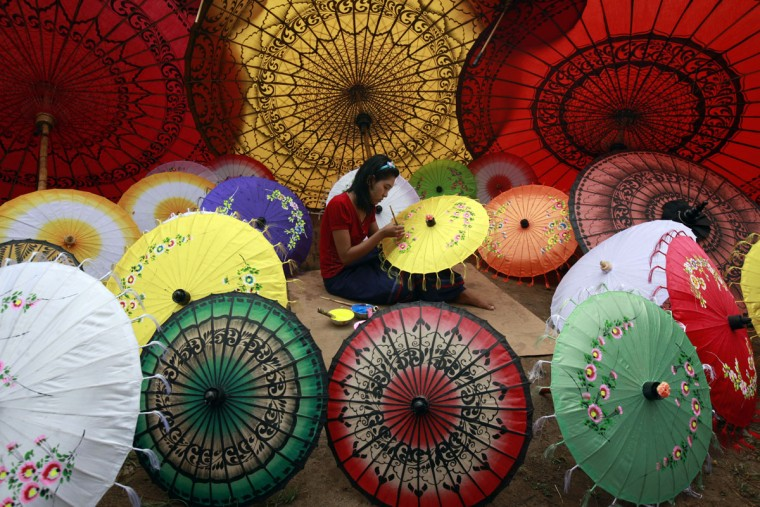 In this photo taken on May 17, 2015, a girl paints on an umbrella in Pathein township, Ayeyarwady Delta, Myanmar. (AP Photo/Khin Maung Win)