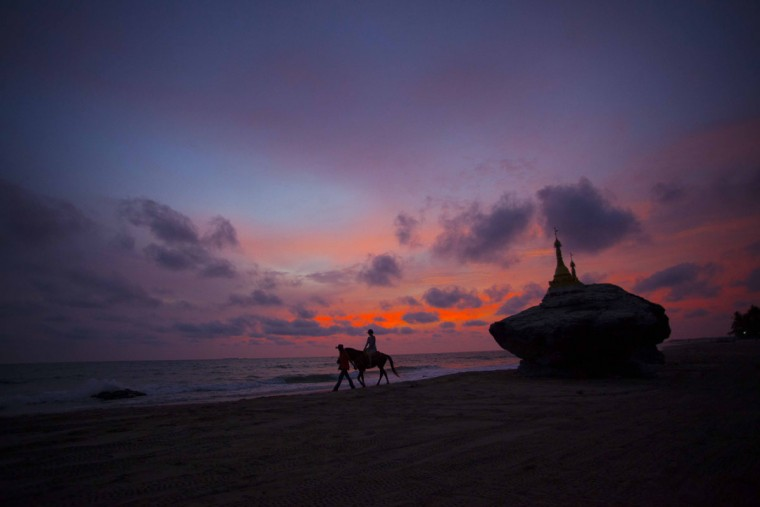 In this May 16, 2015, photo, a visitor rides a horse near pagodas at Ngwe Saung beach, Pathein township, about 145 miles from Yangon, Myanmar. (AP Photo/Khin Maung Win)