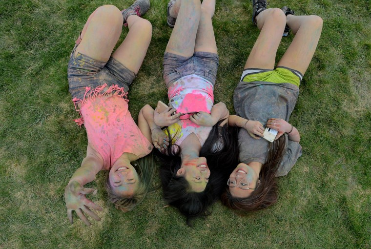 From left, Utica College freeman students Trang Doan, Linh Bui, and Megan Vo take a rest from throwing colored powder during the Holi Festival of Colors celebration on their campus, Friday, May 1, 2015 in Utica, N.Y.. The event celebrates cultural diversity with students throwing colored powder into the air in a large group. (Mark DiOrio/Observer-Dispatch via AP)