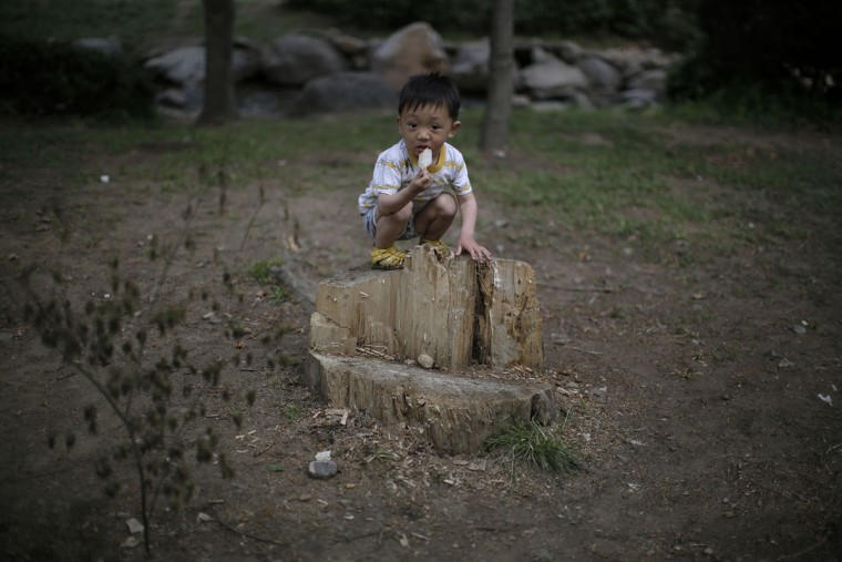 A child squats on a tree stump while eating his ice-cream at the Moranbong or Moran Hill, Sunday, May 3, 2015 in Pyongyang, North Korea. (AP Photo/Wong Maye-E)