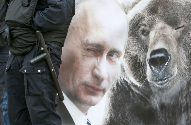 A security officer stands guard near a poster depicting Russian President Vladimir Putin in St.Petersburg, Russia, Friday, May 1, 2015. (AP Photo/Dmitry Lovetsky)