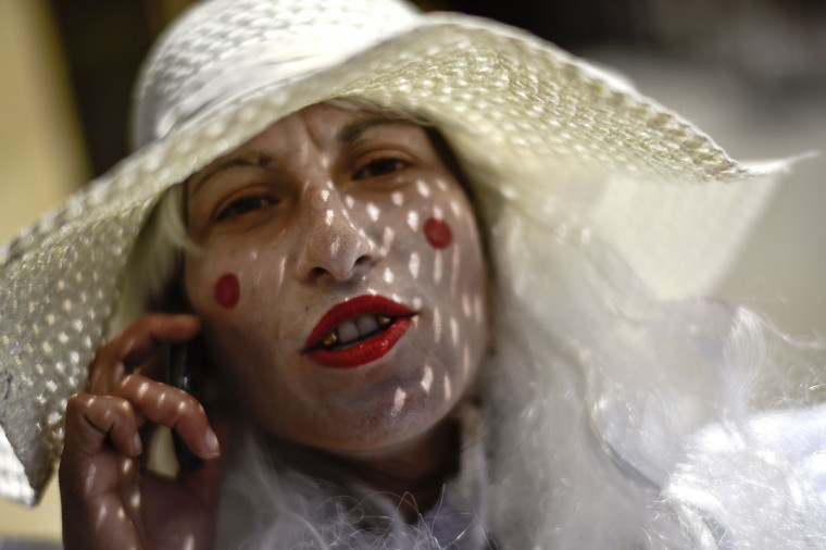 Twenty year old Marina, speaks on a cellular phone as she begs on the street, made-up as a clown, in Pamplona, northern Spain, Wednesday, May 27, 2015. (AP Photo/Alvaro Barrientos)