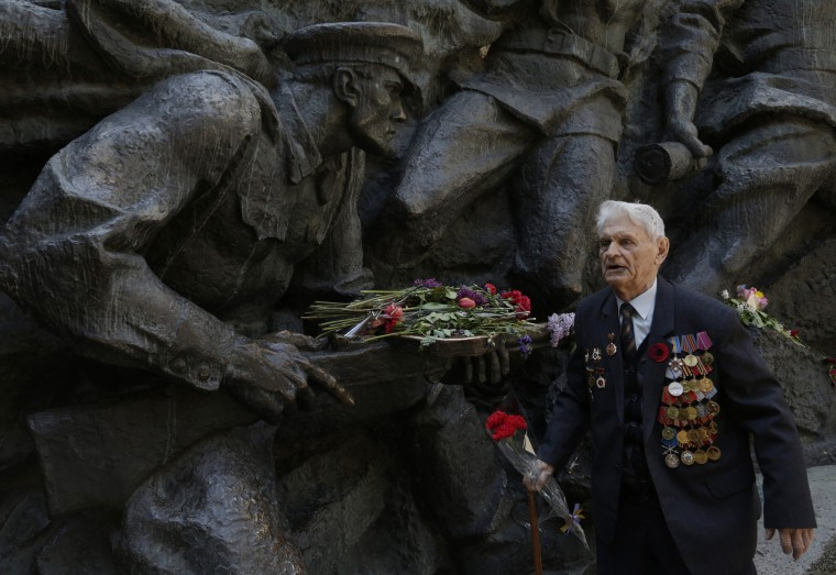 A Veteran walks past a sculpture in Kiev on May 9, 2015 before a ceremony marking the 70th anniversary of the end of World War II. Tanks and rocket systems rolled through the rebel bastion of Donetsk in east Ukraine as pro-Russian insurgents feted 70 years since victory over Nazi Germany in the war. Imitating a vast military parade being held simultaneously in Moscow, some 1,500 separatist fighters marched through the rebel-held city clutching red Soviet flags and several portraits of Stalin. (Anatoli Stepanov/AFP-Getty Images)
