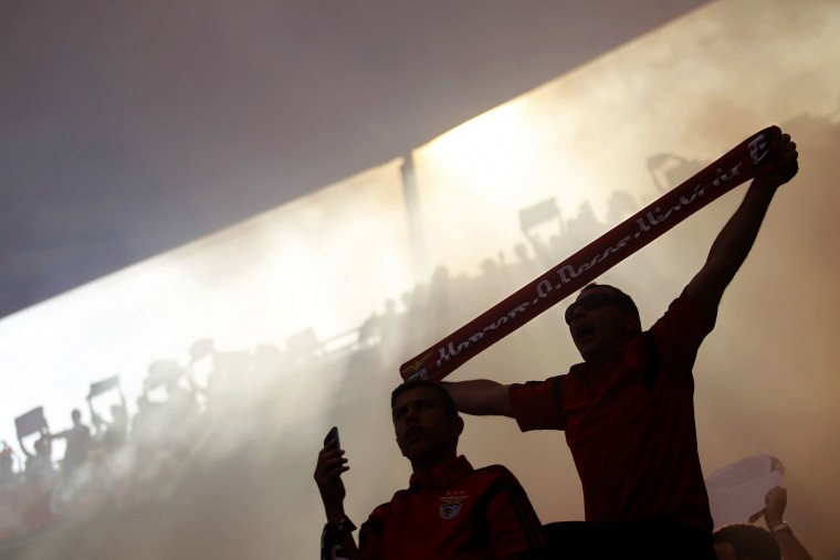 Smoke surrounds fans of Benfica as they cheer prior the Portuguese league soccer match between Benfica and Penafiel at Benfica's Luz stadium, in Lisbon, Portugal. Benfica won 4-0. (Francisco Seco/Associated Press)